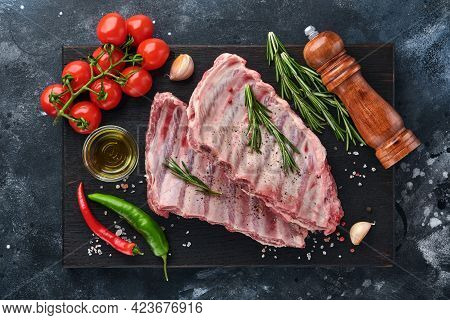 Raw Pork Ribs Or Fresh Uncooked Meat With Spices On Black Wooden Tray With Paprika, Garlic Cloves An