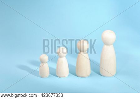 Wooden Figurines Standing In A Row From Low To High. Person Growth On Blue Background. Management St