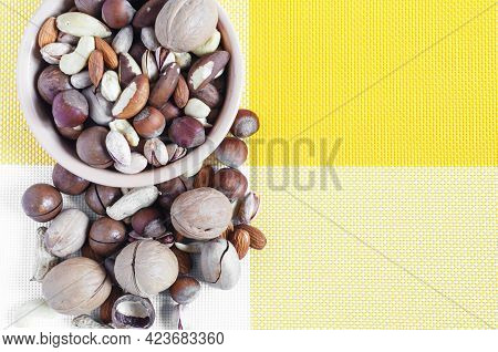Nuts In Ceramic Dishes And Nuts Scattered On A Yellow And White Textile Background Top View Assorted