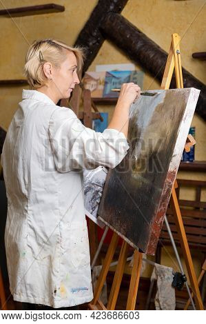 Happy Woman Paints On Canvas Using Thin Brush. Canvas Stands On The Easel. Artist Draws At Easel. Si