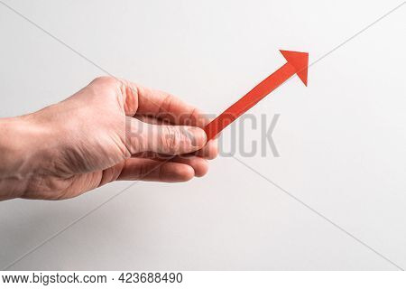 Hand Holding A Red Paper Arrow Pointing Up To The Right