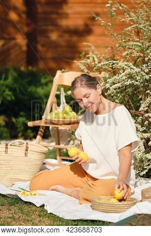 Happy Girl In Linen Clothes Sits In The Garden On A White Blanket And Holds Lemons In Her Hands.
