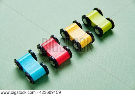 Toy Cars Made Of Wood Of Different Colors Are Stand In A Row.