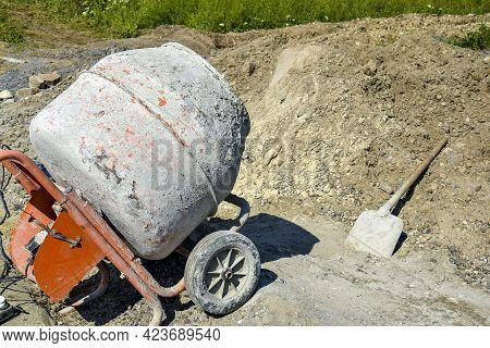 Mobile Concrete Mixer On Background Of Pile Of Gravel. Preparatory Work For Preparation Of Concrete