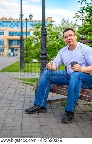 A Satisfied Person Sits And Eats A Bun, A Donut, Cookies With Tea, Coffee In A City Park On A Bench,