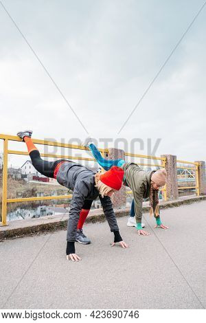Two Young Women Friends Stretches During Workout, Fit Girls Exercising And Doing Stretching Exercise