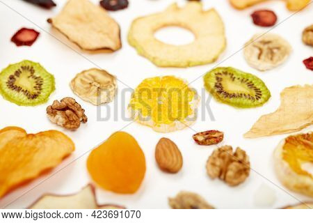 Close Up Of Healthy Food Dried Apples, Orange, Dried Apricots, Kiwi, Dried Coconut And Walnuts On Wh