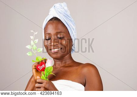 African Girl Standing On Gray Background, Bath Towel Knotted On The Head While Admiring A Flower Smi