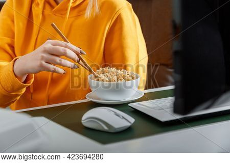 Woman Eats Noodles With Chopsticks Behind Computer At Home Workplace, Home Office During Video Game