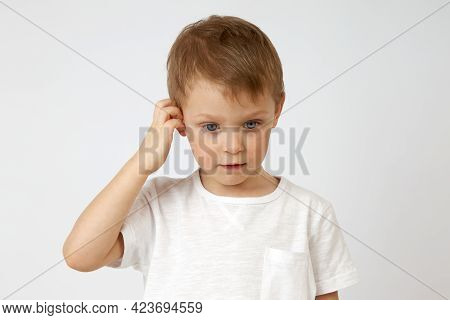 Little Boy With Blue Eyes Is Deep In Thought, Looking Down And Scratching His Head Against A White B