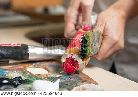 Creative Female Painter Mixes Palette Of Oil Paints In Palette. Close-up View. High Quality Photo