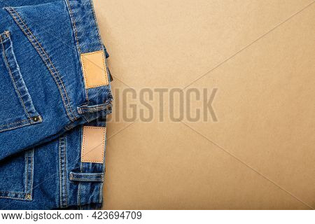Classic Blue Jeans. Casual Pants Clothing Blue Jeans With Brown Blank Leather Labels On Beige Craft