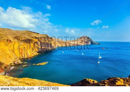 The west coast of Madeira - the bay between the rocks with yachts and boats. Madeira is island in the Atlantic. The blinding midday sun. The concept of active, ecological and photo tourism