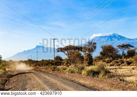 Dirt road in Amboseli park. The famous snow-capped Mount Kilimanjaro in the flat savannah. Plain acacias of the Horn of Africa. Travel to exotic Africa.