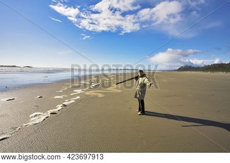 The woman-photographer with photographic equipment in hands on coast of ocean