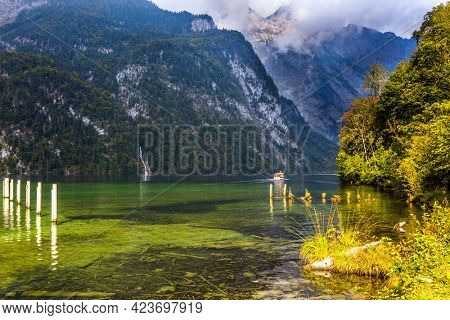 The lake Konigssee in Germany is surrounded by high mountains. Mooring piles for tourist boats. Wonderful trip on the lake tourist boat. The concept of active, ecological and photo tourism