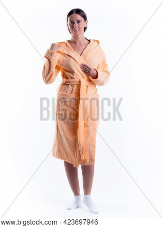 Woman In A Bathrobe On An Isolated White Background With A Smile On Her Face.