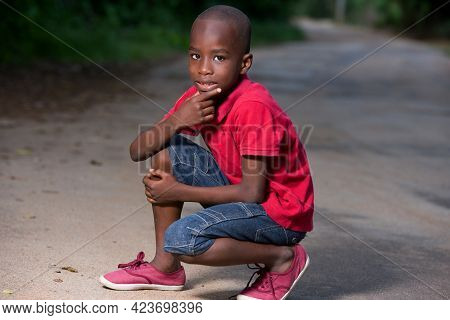 Little Boy In Red Shirt Squatting On A Lane And Watching The Camera With His Hand Under The Chin.