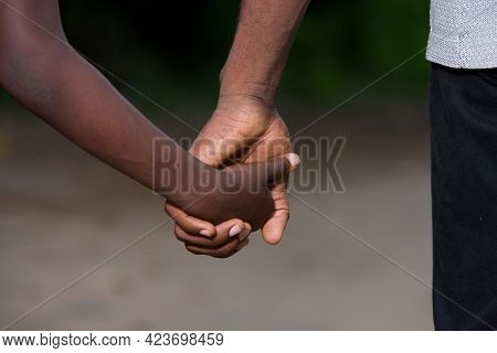 Father And Little Son Holding Hands Walking On A Road. The Father's Hand Lead His Son Into The Wild