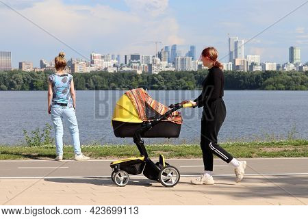 Moscow, Russia - June 2021: Woman With Baby Pram Walking On Background Of River And Skyscrapers In S