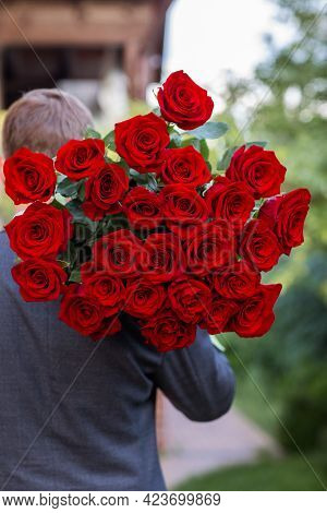 Man In Business Suit Is Caring Big Bouquet Of Red Roses At His Shoulder. View From The Back