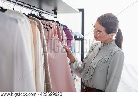 Designer Looking At Dress On Hanger In Atelier.