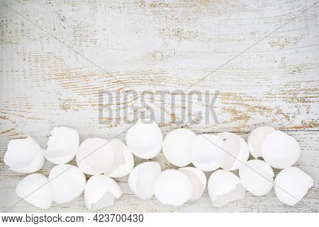 Lots Of Broken White Eggshells On A Light Wooden Background. Copy Space.