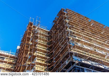 Scaffolding On The Facade Of A High-rise Building Under Construction. Construction Of Multi-storey B
