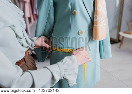 Cropped View Of Seamstress Measuring Pocket Of Blazer In Atelier.