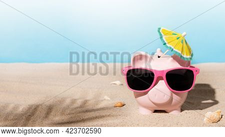 Piggy Bank With Sunglasses And Sunshade Umbrella On A Sandy Beach. Savings For Summer Vacation Or Su