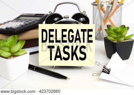 Delegate Tasks. The Inscription On The Sticker On The Alarm Clock Near The Calculator And Flowerpots
