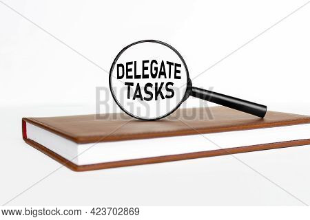 Delegate Tasks. Text On Magnifier Glass. Magnifier On Notepad On White Background