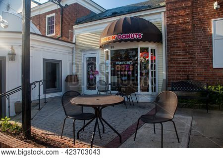 NEW CANAAN, CT, USA- JUNE 13, 2021:  Dunkin Donuts entrance with little table outdoor near Elm Street