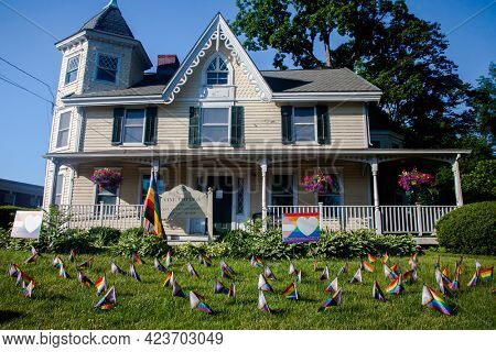 NEW CANAAN, CT, USA- JUBE 13, 2021: Vine cottage building on Main Street with little pride flags on front yard