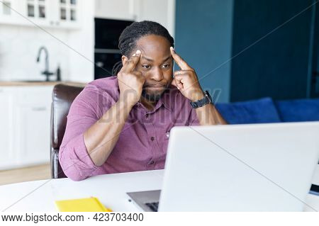Concentrated African Male Freelancer Using Laptop For Remote Work At Home, Dark Skinned Man Absorbed