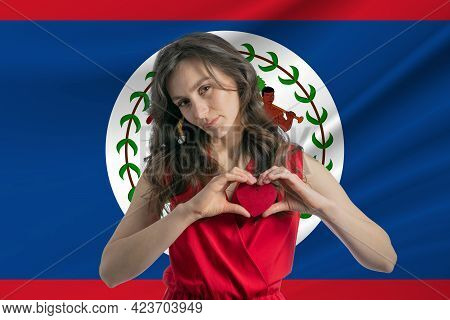 Love Belize. A Girl Holds A Heart On Her Chest In Her Hands Against The Background Of The Flag Of Be