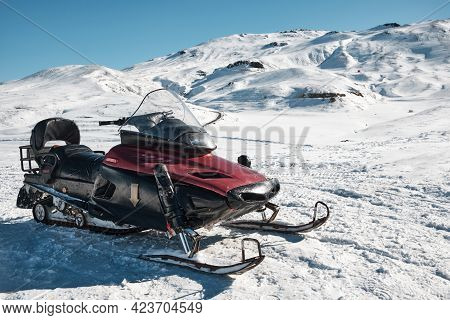Snowmobile Against Snow Covered Slope At Background. Snow Vehicle