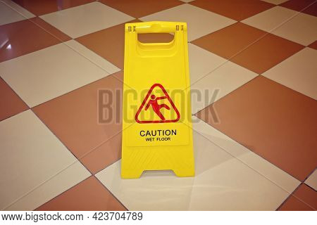 Yellow Sign With The Words Caution Wet Floor On Tiled Floor. The Concept Of Cleaning, Cleaning Servi