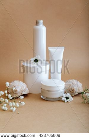 Set Natural Beauty Cosmetic Skincare Products With Flowers Sea Shells On Beige Background. Female Wh