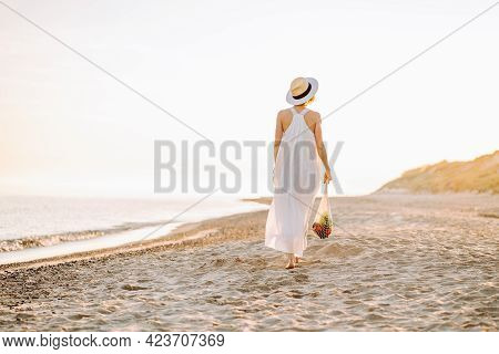 Reusable Recyclable Lifestyle Concept. Woman In Natural Clothes Walk Along A Beach And Hold Reusable