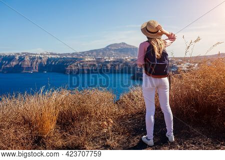 Traveler Woman Walking On Santorini Island, Greece Enjoying Landscape. Happy Hiker With Backpack Enj