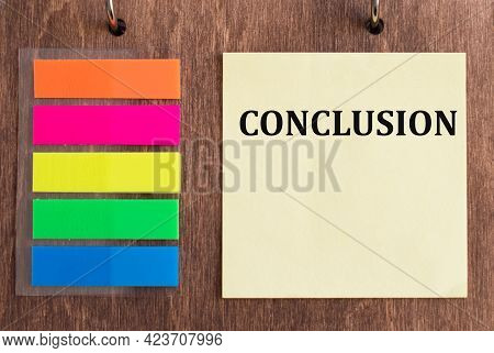 Card With Text Conclusion On A Wooden Background Next To Colored Adhesive Stickers