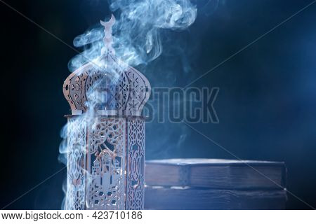 Ornamental Arabic lantern with with Holy Quran. Festive greeting card for Muslim holy month Ramadan Kareem.