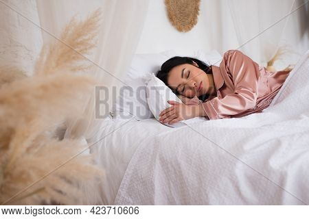 Pretty Young Asian Woman In Silk Pajamas Sleeping In Bed With White Linen In Bedroom