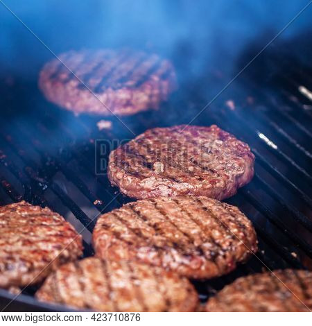 Process Of Preparing Hamburgers On An Outdoor Grill. Bbq Grill With Roasted Meat In Smoke