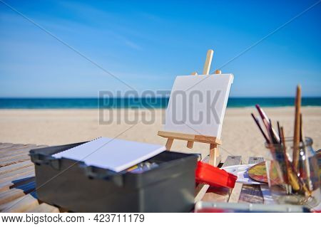 Easel With Canvas On The Sea Background. Concepts Of Art, Hobby And Painting In Open Air. Creativity