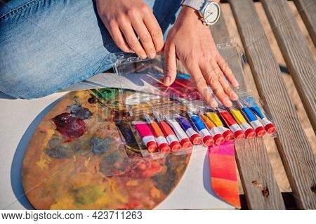 Close-up Of Female Artist Hands On A Painting Palette And Tubes With Paints On A Wooden Surface