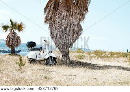 Messina, Sicily, Italy - June 13 2021: Iconic Italian Designed Scooter Vespa Parked On The Sand Beac