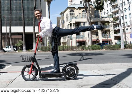 Happy Man Businessman Riding Electro Scooter On Cityscape Background, Rental Transportation.
