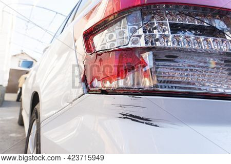 Big Black Scratch On Rear Bumper And Broken Taillight On White Car Due To Car Crash, Unsafe Driving,